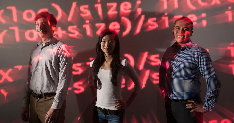 Ashley Han, a science and technology major, stands with professors Colin Milburn (left), incoming chair of the Science and Technology Department, and Gerardo Con Diaz of the Science and Technology Department.  They stand in red computer code because the work that Han and Diaz have been doing is on computer programs.