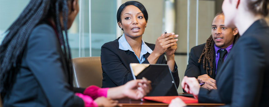 Woman looking at colleague across conference table