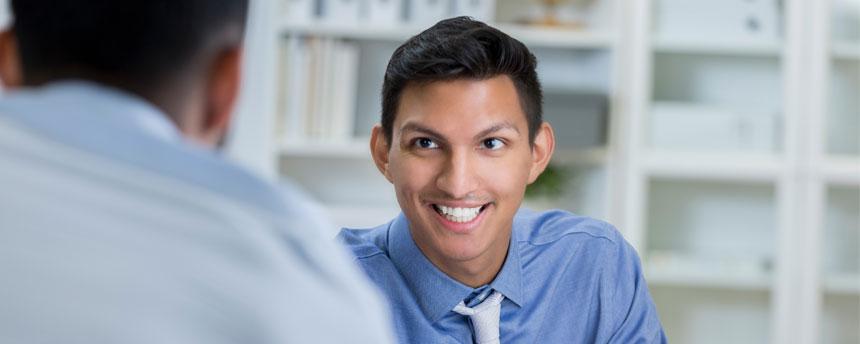 Man smiling behind desk