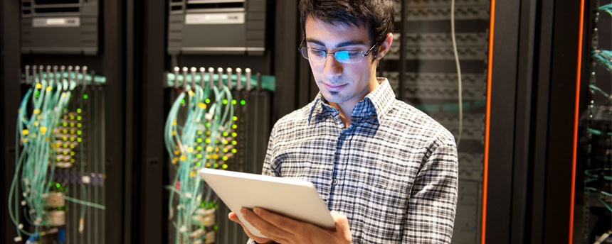 Man looking at tablet in front of servers
