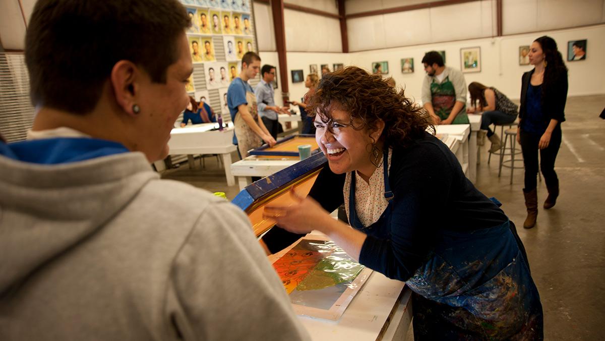 UC Davis student Gilda Posada, right, helps Ricardo Pizano with screen prinking