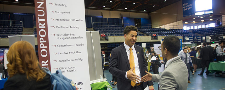 Two men talking in a big career fair with others milling about