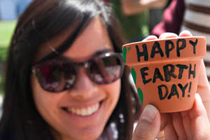 """A woman holds up a painting that reads """"Happy Earth Day"""""""