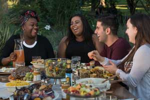 Three women and a man share a picnic dinner - One Health Blog
