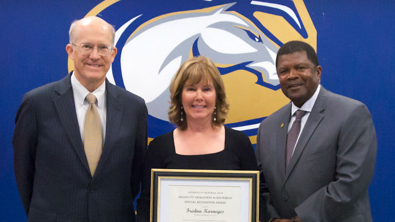 Fredna Karneges holds award plaque; she is flanked by Ken Burtis and Walter Robinson.