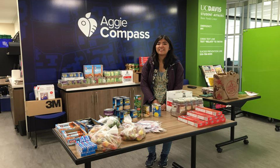 Woman stands at table offering food, at Aggie Compass.