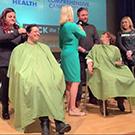 Volunteers have their hair shaved.