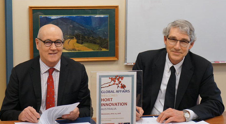 Two men at table, signing document