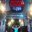 Anna Shumaker poses in front of American Ninja Warrior sign.