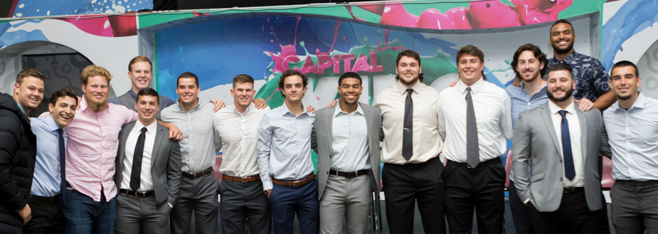 Student-athletes in dress shirts, some with ties and jackets, in a line