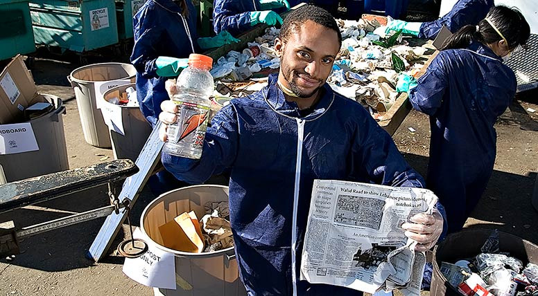 Man holding recyclable materials in an area where people are sorting