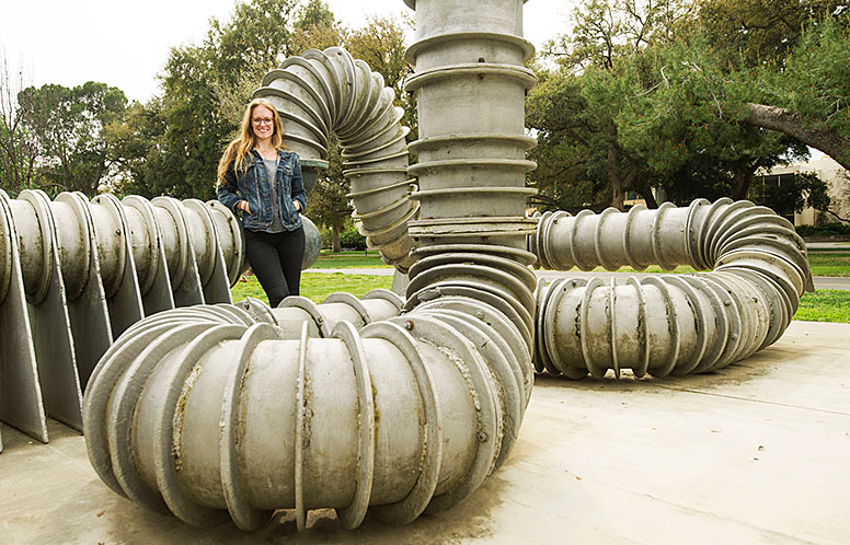 Woman standing on large pipe structure