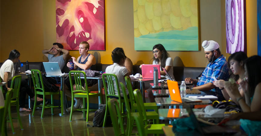 Small groups of students talking and studying in cafe