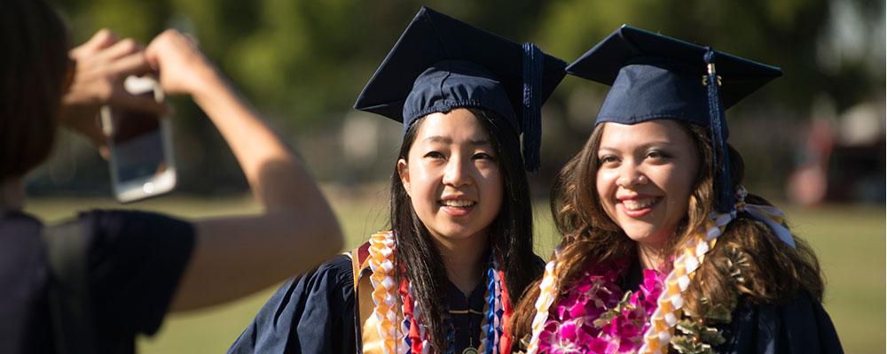 Two women in graduation garb getting a photo taken