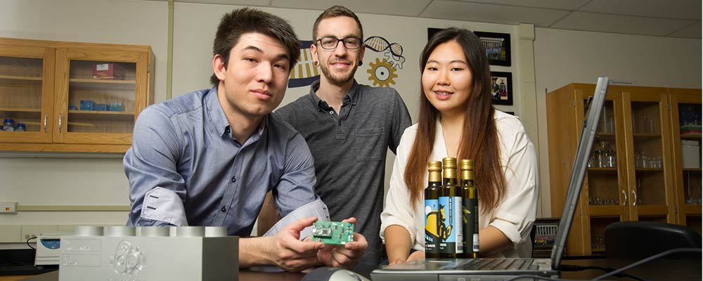 Two men and a woman posing with olive oil and a circuit board