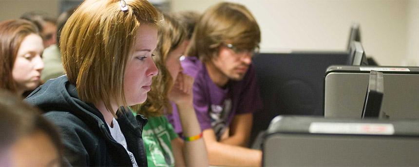 A row of students at computers working