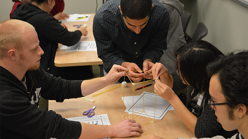 Student and pupils work with spaghetti and marshmallows for a team-building exercise