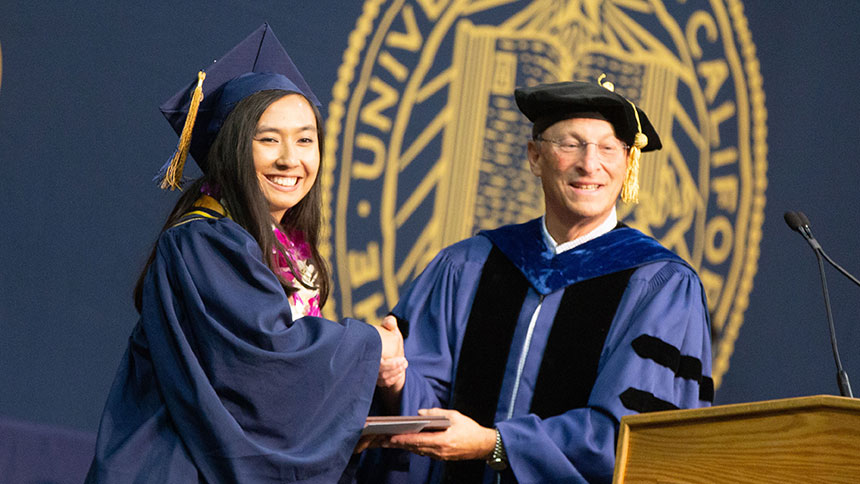 Ralph Hexter, provost and executive vice chancellor, presents an award to Emily Eijansantos at  commencement