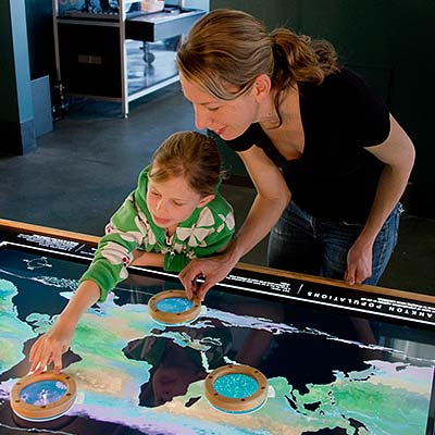 Mother and daughter playing on a lighted surface showing oceans