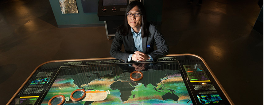 Professor Kwan Liu Ma sitting at a lit table showing the world with oceans and continents