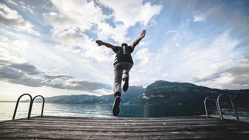 A student jumping off dock at a lake near Florence, Italy