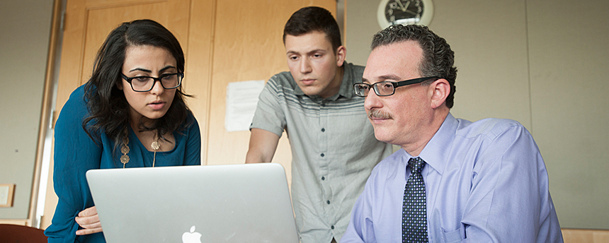 Male professor at computer with woman and young male listening to him