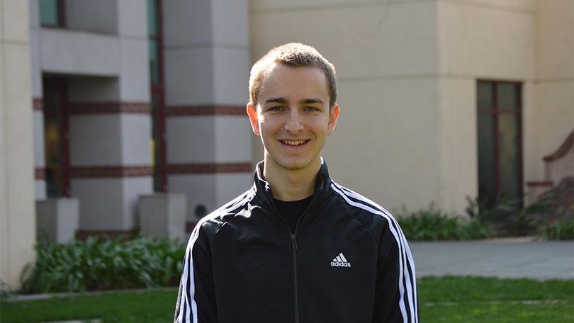 Max Nedorezov stands outside
