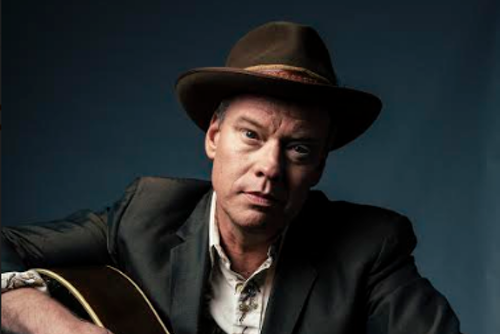 A photo of Shawn Mullins wearing a fedora and holding his guitar.