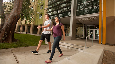 Two students walk in front of Cottonwood Hall