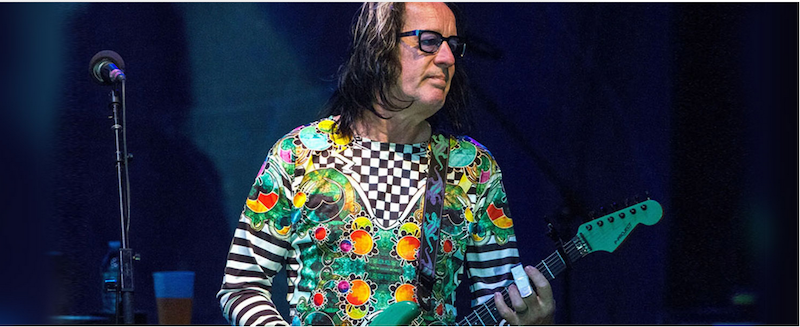 Todd Rundgren playing the electric guitar on stage.