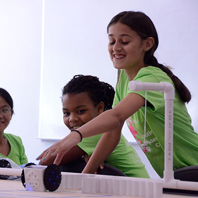 two girls adjust the settings on their project