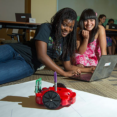 Two SMASH participants program a robot to accomplish simple tasks