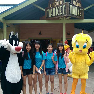 a group of students poses with syvlester the cat and tweety bird